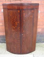 Oak and mahogany bow fronted corner cupboard